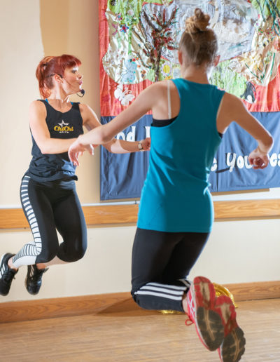 Dance instructor jumping & leading class
